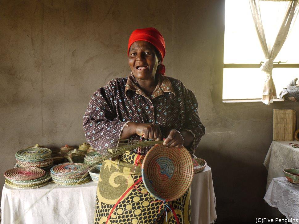 マレアレア村のクラフトショップで籐の籠を編む女性