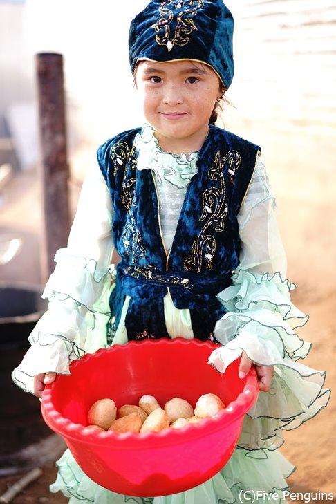 バウルサク(揚げパン)を持つカザフ族の女の子