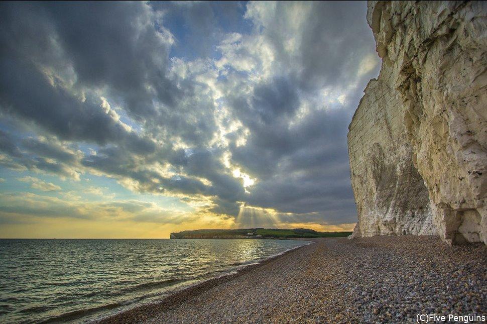 雲の合間から指す沈む太陽の光が、白亜の美しさを際立たせています…。