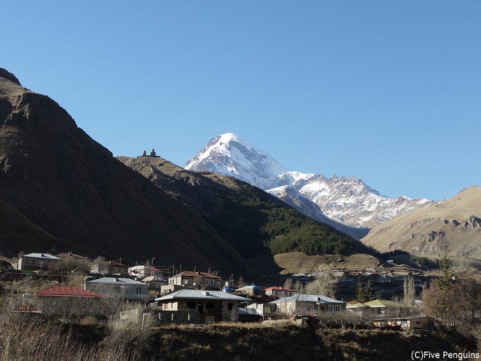 堆雪のカズベキ山と、手前の山の頂上に小さく見えるのがツミンダ・サメバ教会